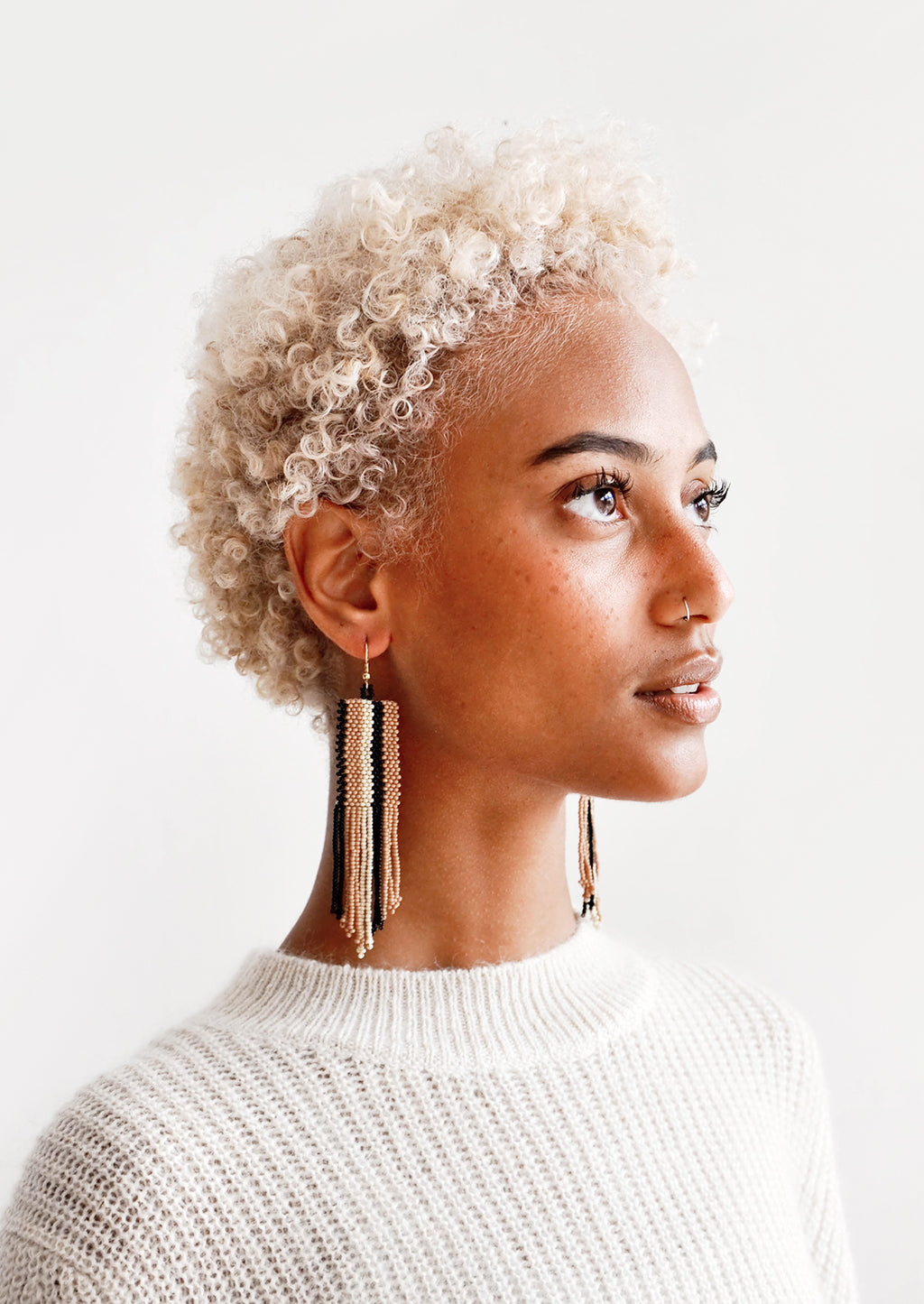 2: Model wears brown, black, and white striped fringe earrings and white sweater.