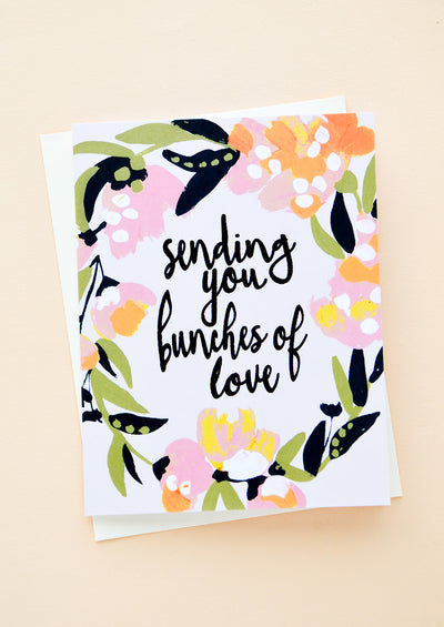 "Floral printed greeting card with black script at center reading ""sending you bunches of love"""