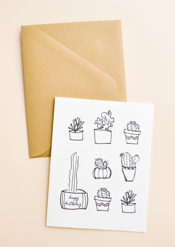 1: White notecard with several drawings of cactus plants, with brown envelope.