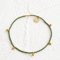 Olive: Bracelet made from olive colored glass seed beads with brass ball accent charms and logo tag