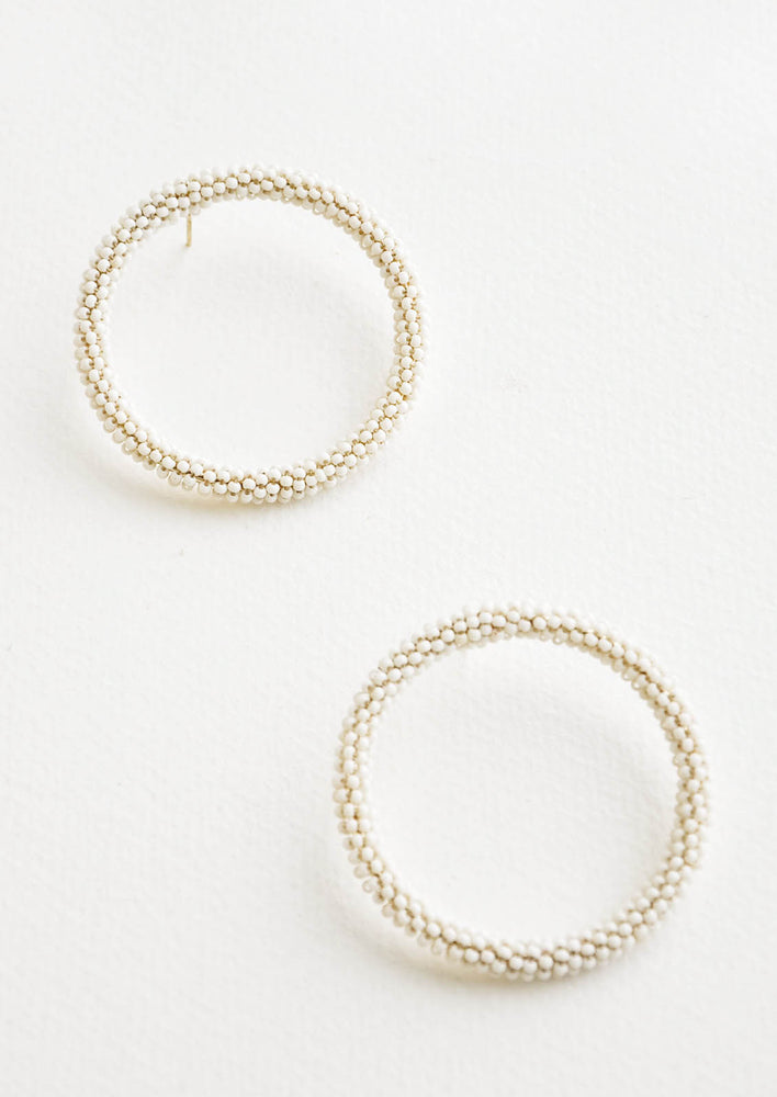 2: Ivory beaded hoop earrings featuring a side silhouette on a post back.