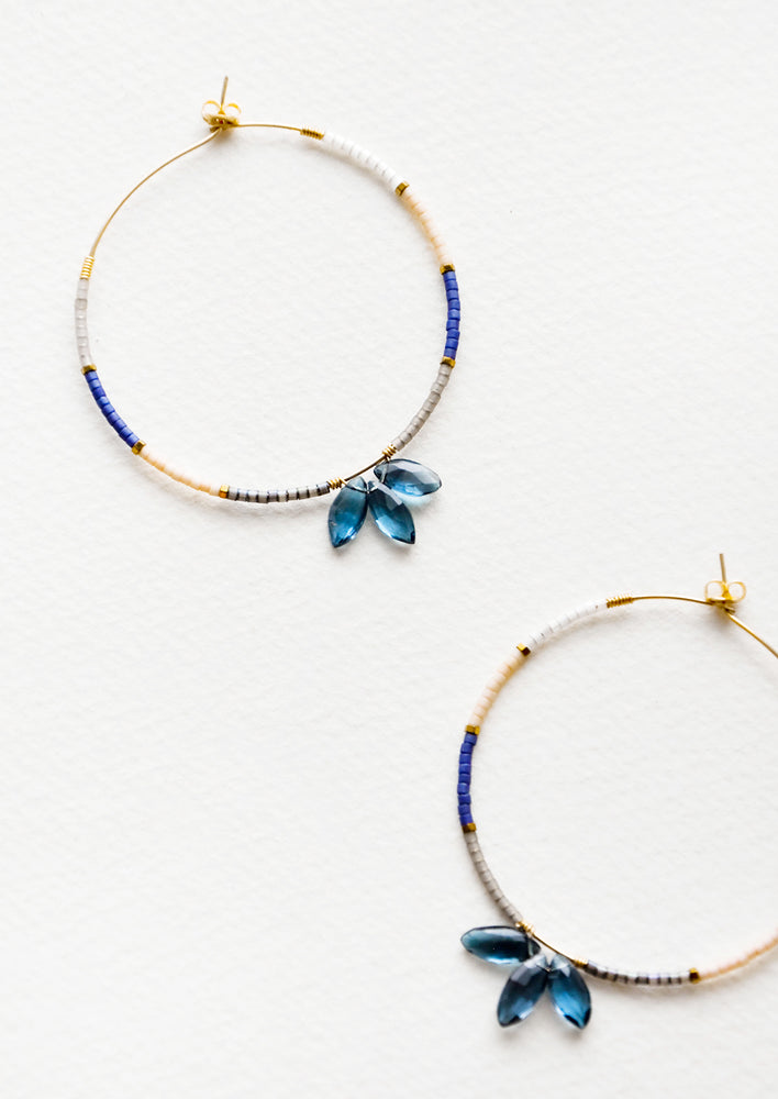 1: Delicate hoop earrings of blue and pink glass beads featuring a trio of larger blue beads at bottom center.