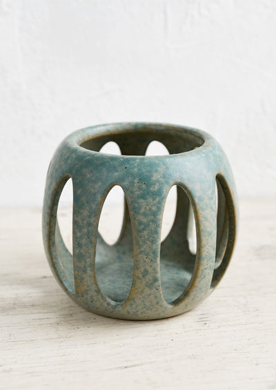 A blue-green ceramic votive holder with petal-shaped cutouts.