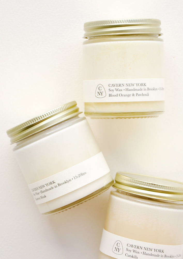 1: Three white glass jars with gold lids, and white labels with black text