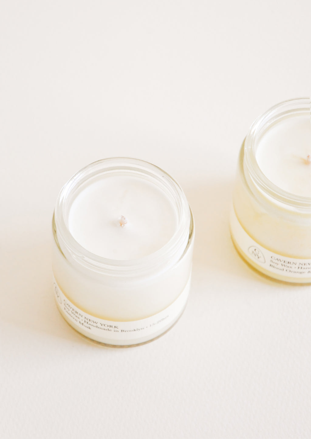 2: Two glass jars with white candle and wick inside