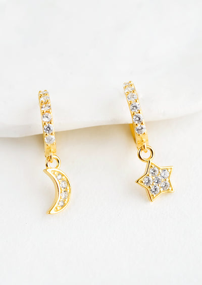 A pair of gold earrings in shape of moon and star with clear crystals.