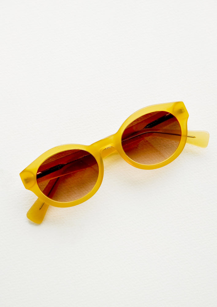 1: Yellow sunglasses with oval-shaped tinted lenses.