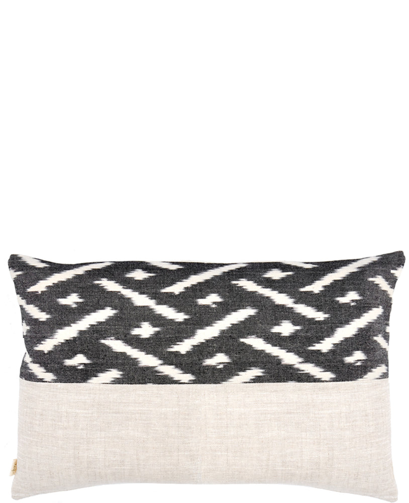 Rectangular throw pillow with black and white ikat patterned top half and natural linen bottom half