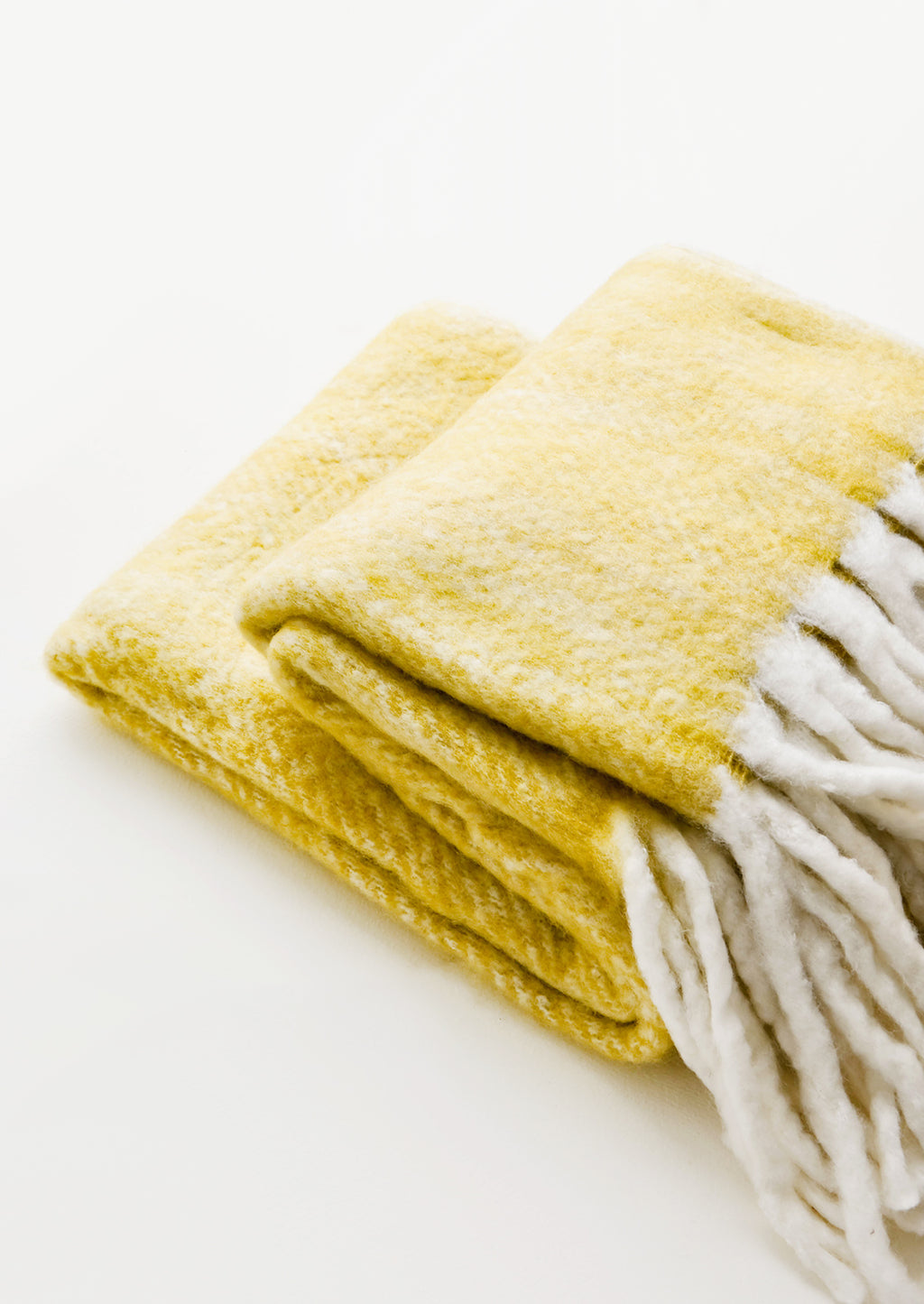 1: Plush and wooly yellow throw blanket with exaggerated fringe trim in ivory