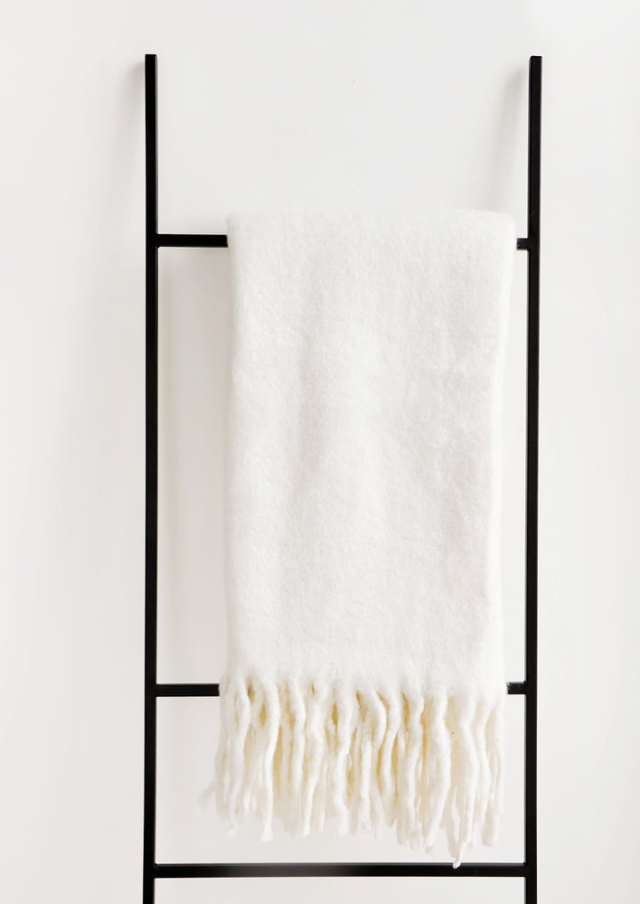 Supernatural: Plush and wooly white throw blanket with exaggerated fringe trim