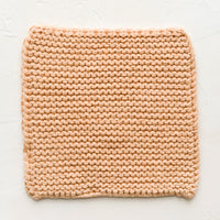Nougat: A square, chunky knit cotton potholder in soft peach color.