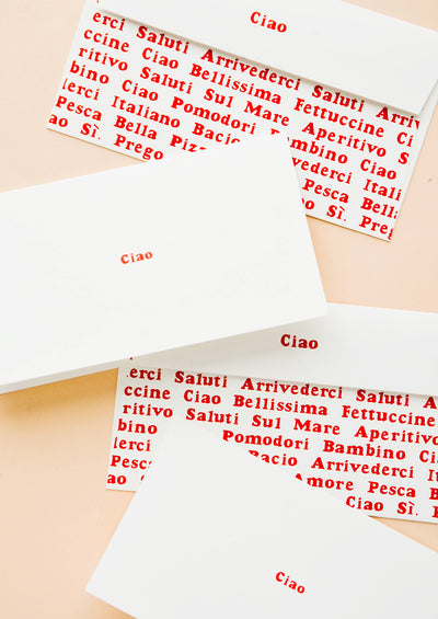 "Stationary set of white folded cards with ""Ciao"" in red text and coordinating envelopes with allover Italian text"