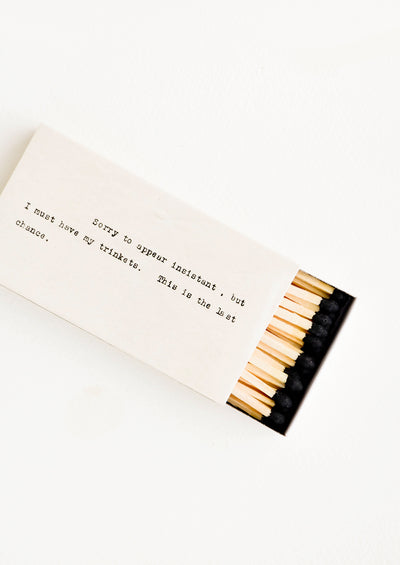 Long matches with black tips in matchbox printed with courier text