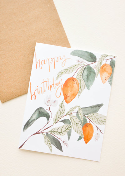 "White notecard with citrus fruit and leaves decoration and the text ""happy birthday"" with brown envelope."