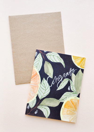 "Notecard with citrus fruits and leaves on black ground and the text ""Congrats"", with brown envelope."