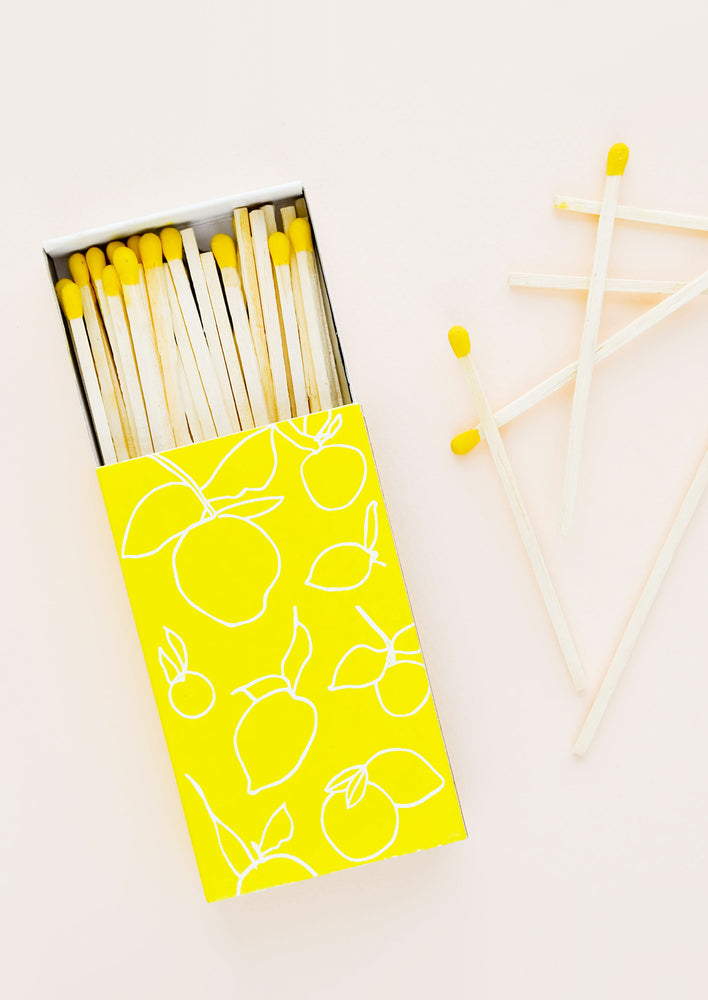 1: A bright yellow matchbox with white lemon outlines printed on it is slid open to display matches with yellow tips.