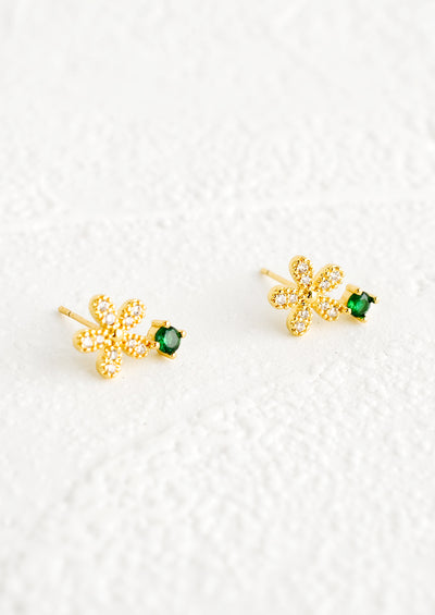 A pair of stud earrings with a gold and crystal flower shape attached to a round emerald colored stone.