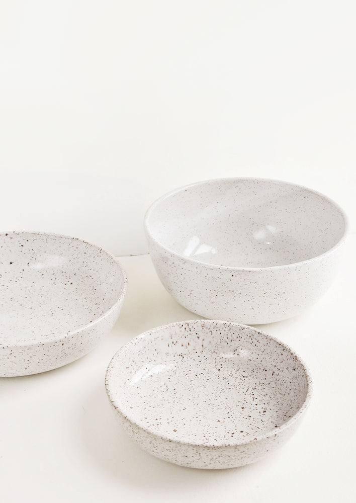 2: A mix of speckled white ceramic bowls in varied sizes.