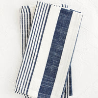 2: White and blue striped cotton napkins, pictured folded as a pair.