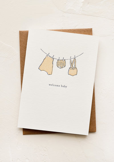 A greeting card with baby clothes hung on a clothesline.