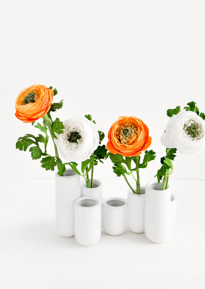 1: Multiple stem vase made of white ceramic vials in varying heights, clustered and fused together. Displayed with ranunculus flowers.