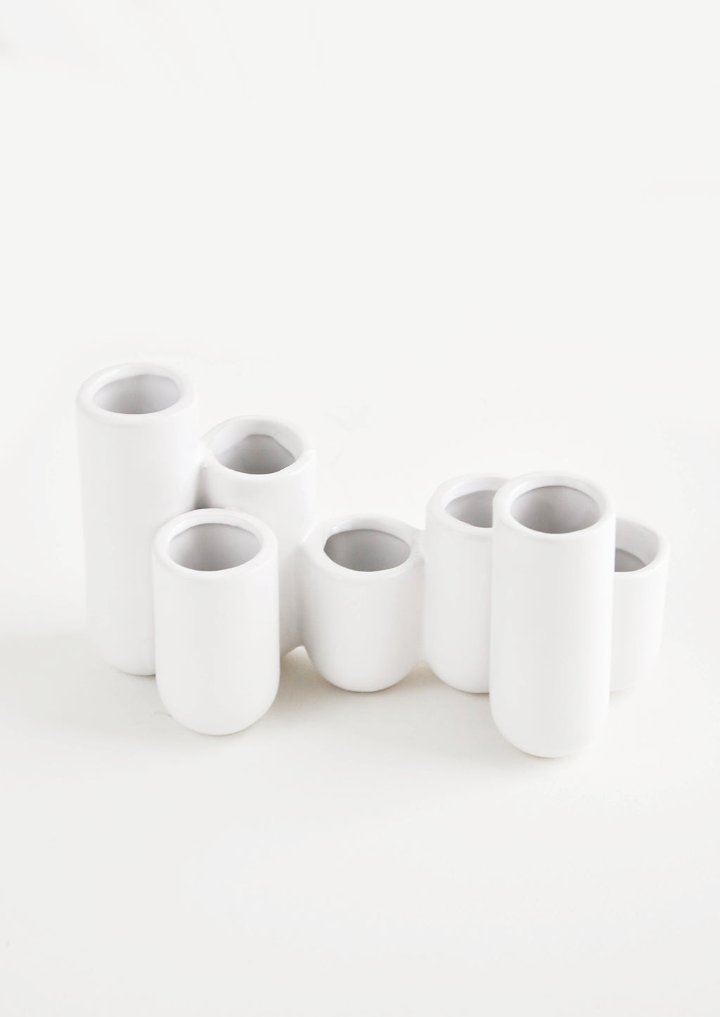 2: Multiple stem vase made of white ceramic vials in varying heights, clustered and fused together