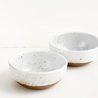 3: Two glossy white ceramic bowls with brown speckles.