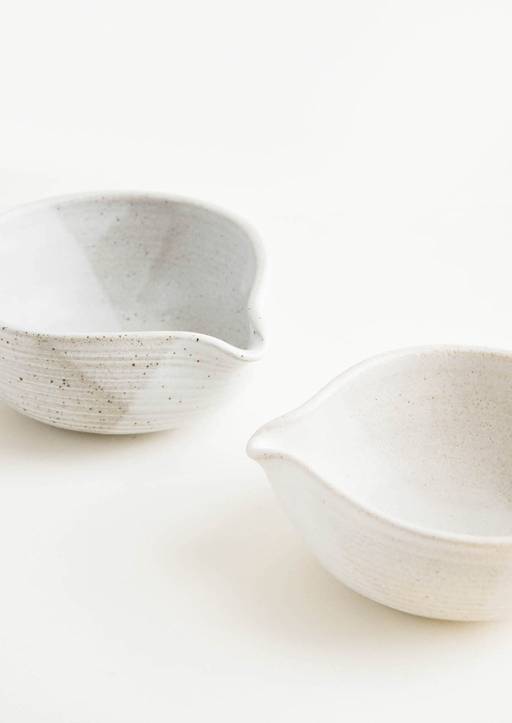 1: Two ceramic spouted bowls in different shades of white.
