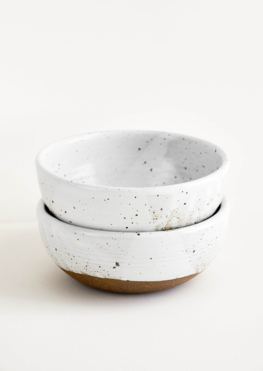 Glossy White / Soup: Two stacked white ceramic bowls with brown speckles.