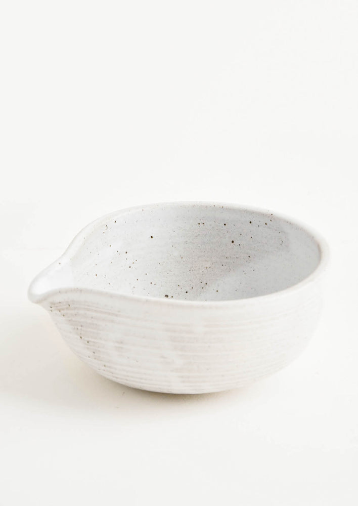 A gray-white spouted ceramic bowl.