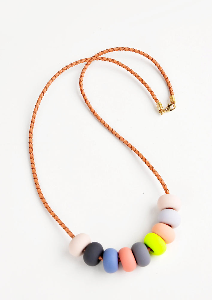 Woven leather cord necklace with gold clasp and rounded clay beads tans, pinks,gray, blue, and neon yellow.