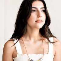 2: Model wears clay bead necklace and white tank top.