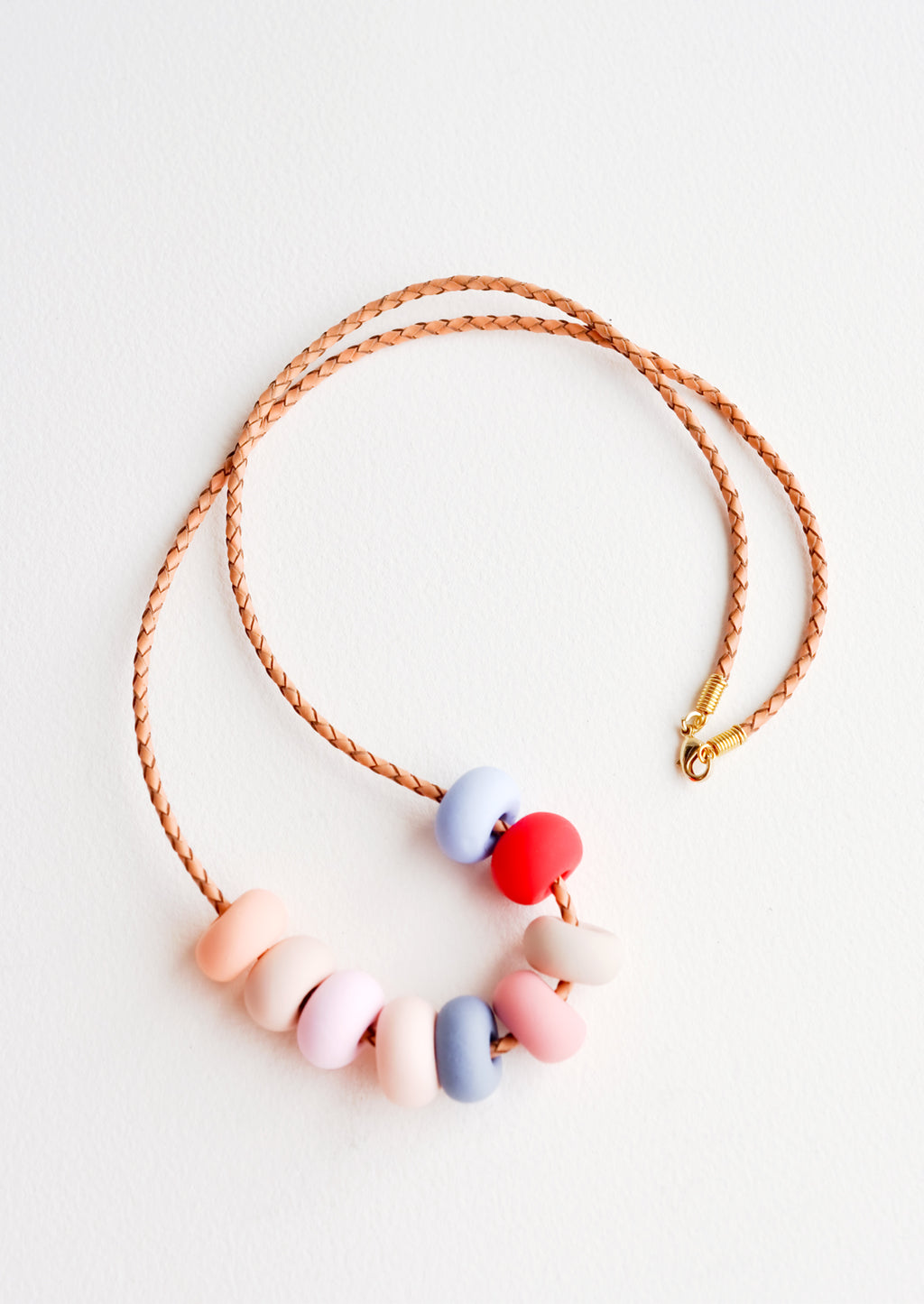 Desert Rose: Woven leather cord necklace with gold clasp and rounded clay beads tans, pinks, red, and blues.