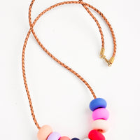 Tropical Fruit: Woven leather cord necklace with gold clasp and rounded clay beads pinks, reds, blues, and purple.