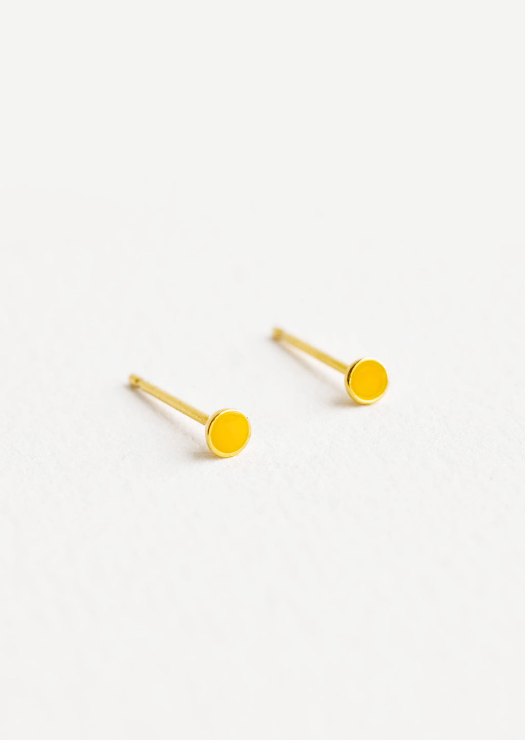 1: Round studs with mustard yellow enamel circle and gold bezel.