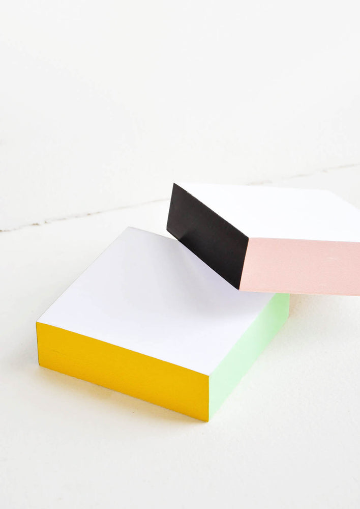 Two small square notepads with white unlined paper, one has edges painted yellow/green, the other is black/pink.