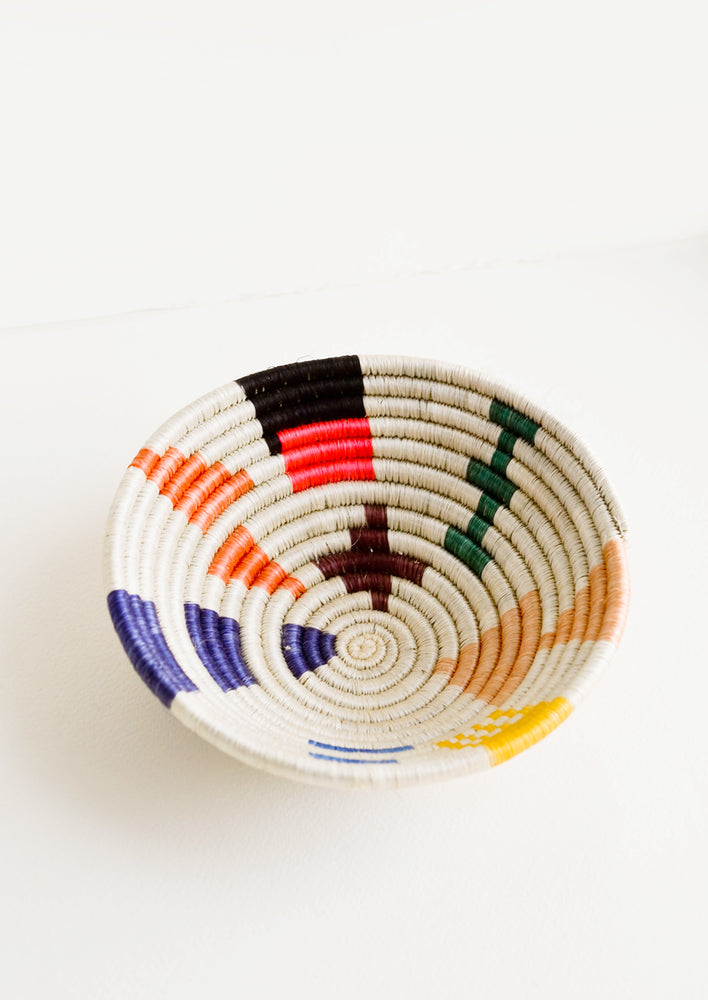 1: Shallow bowl made of woven fiber in a mix of bright colors and geometric shapes
