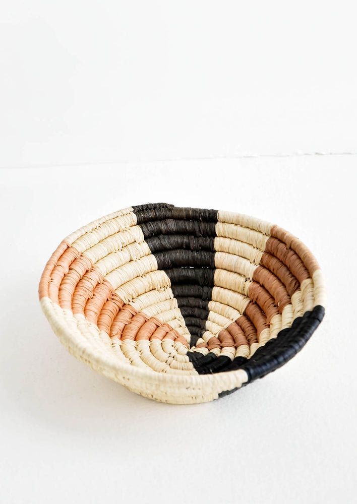 "1: Small woven bowl made from natural fiber, multicolored ""ray"" pattern in neutral hues"