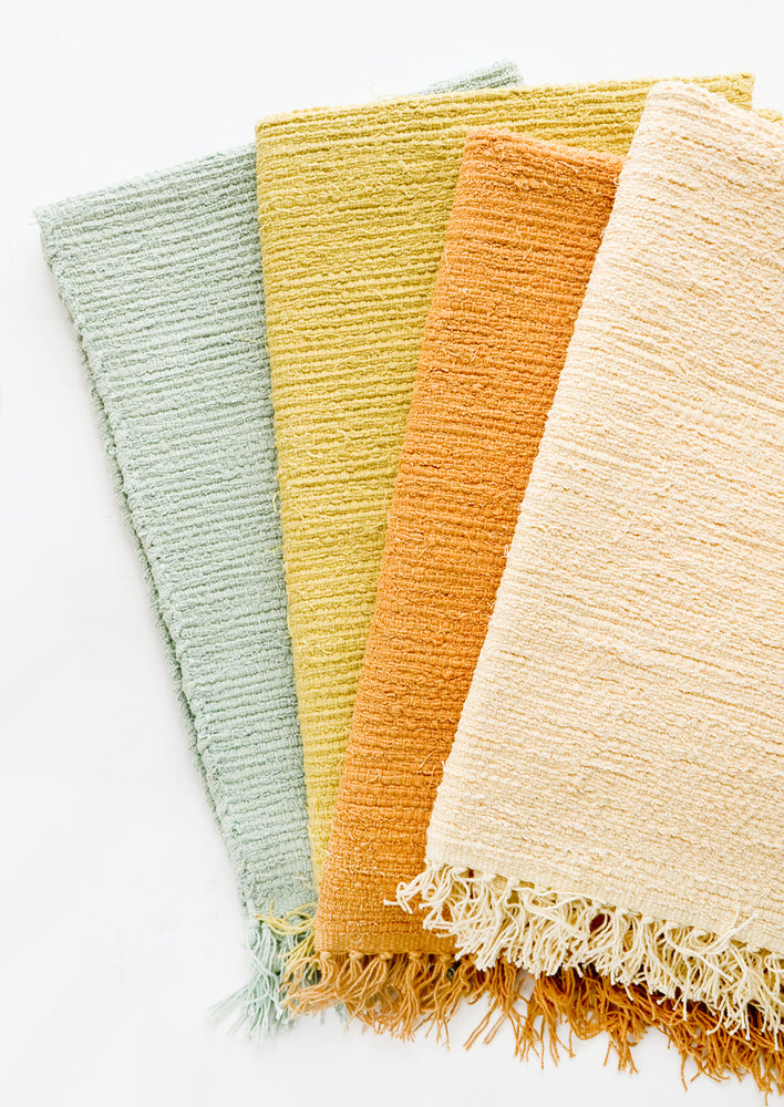Goldenrod: Cotton flatweave rug in solid color with slight texture, fringe trim on two ends