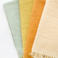 Maize: Cotton flatweave rug in solid color with slight texture, fringe trim on two ends