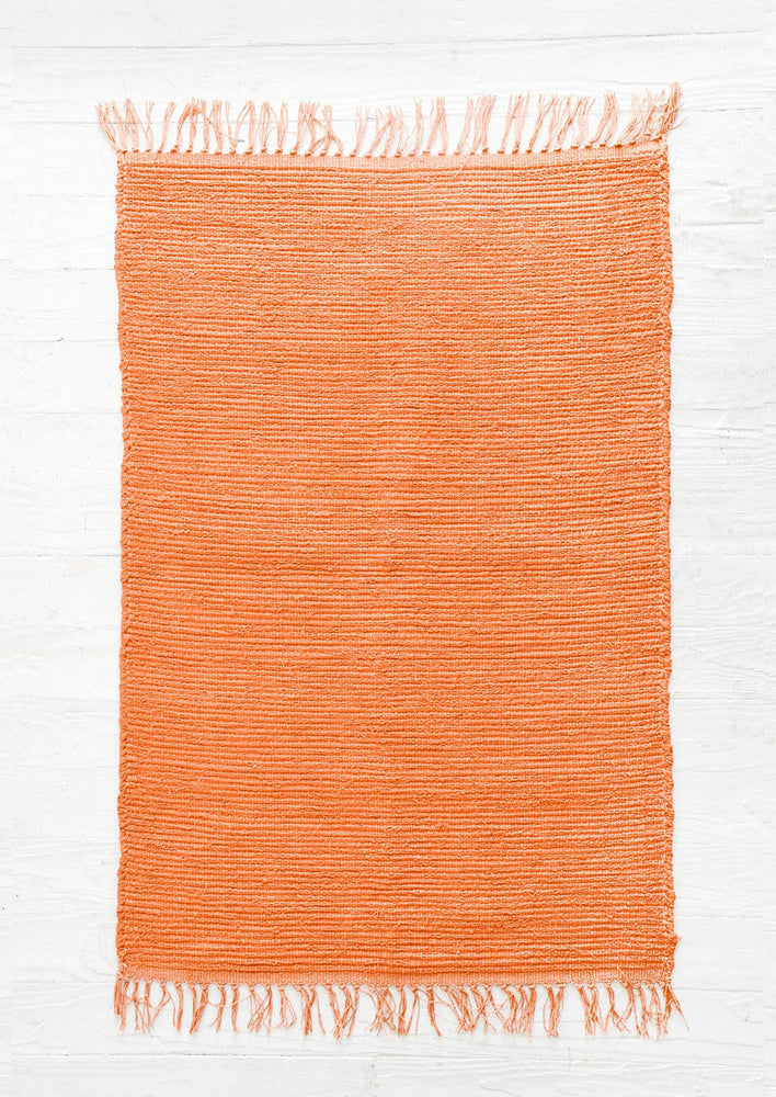 Cayenne: Cotton flatweave rug in solid color red orange with slight texture, fringe trim on two ends