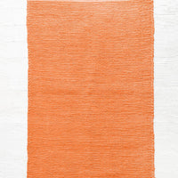 Paprika: Cotton flatweave rug in solid color red orange with slight texture, fringe trim on two ends