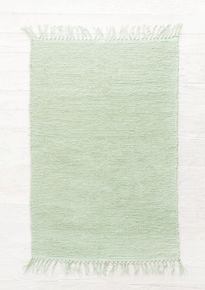 Lagos: Cotton flatweave rug in solid mint green color with slight texture, fringe trim on two ends