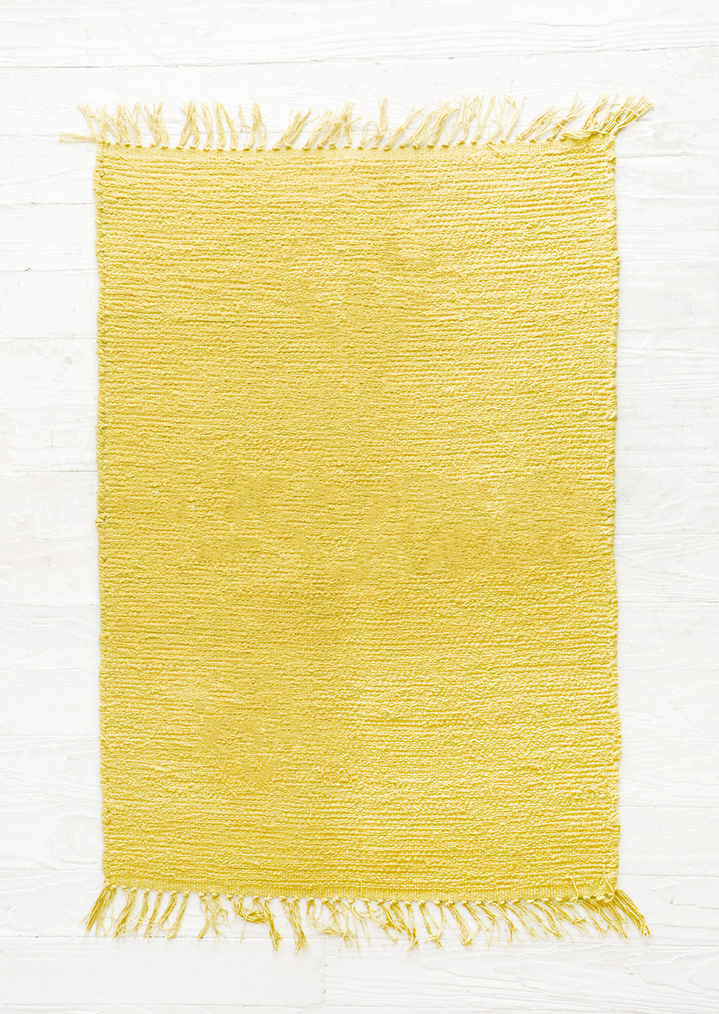 Sulfur: Cotton flatweave rug in solid color yellow green with slight texture, fringe trim on two ends