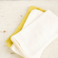 Natural: Folded cotton napkins in natural and chartreuse on a rustic table