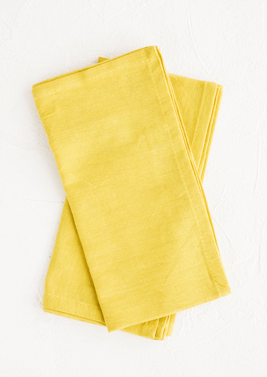 1: Pair of folded cotton napkins in chartreuse hue