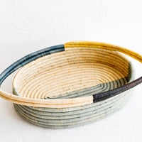 1: Oval bread basket in woven raffia with protruding handles at either side. Blue and yellow colorblock pattern.