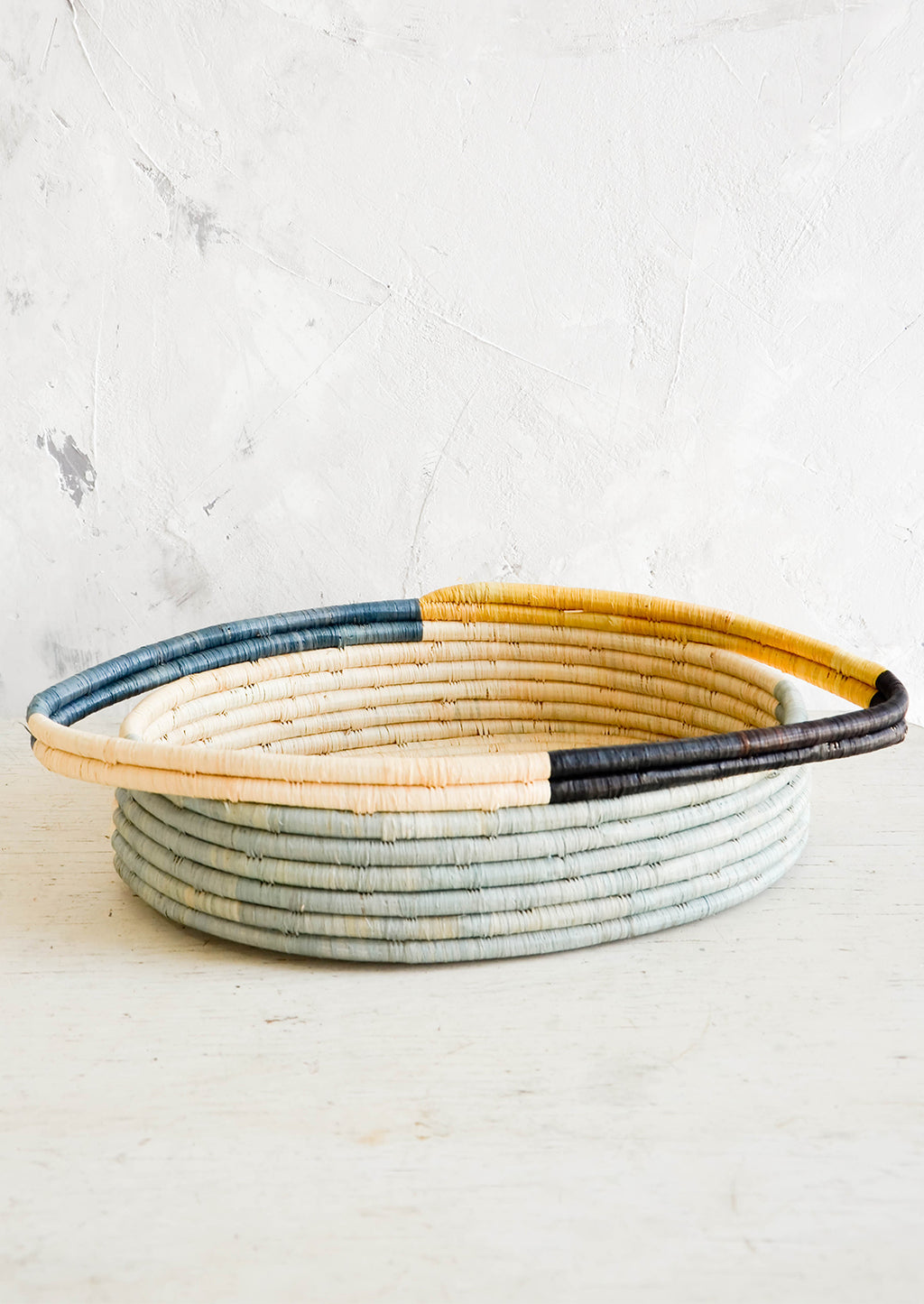 2: Oval bread basket in woven raffia with protruding handles at either side, sitting on a table.