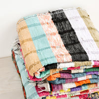 2: Stack of recycled cotton floor blankets in colorful stripes