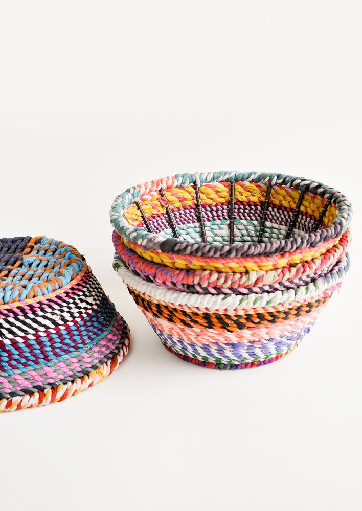 2: A stack of multicolored striped fabric bowls sits next to an overturned one.